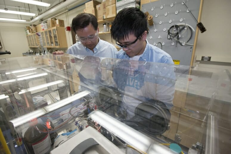 Professor Song Jin, left, and graduate student Wenjie Li observe their lab-scale device for storing and releasing solar energy. DAVID TENENBAUM